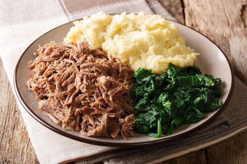 A Zimbabwean meal consisting of stewed beef with pap porridge and spinach.