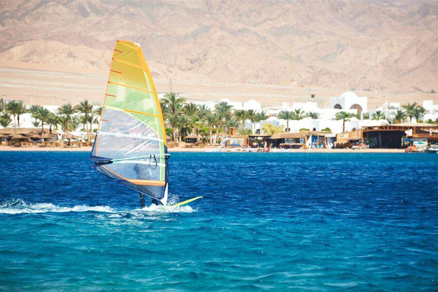 A windsurfer sailing off the blue coast of Dahab