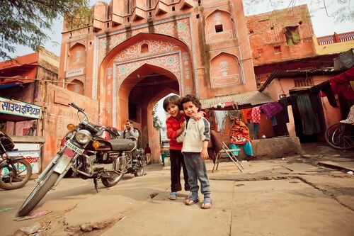 Children pose in front of a traditional Jaipur pink gate.
