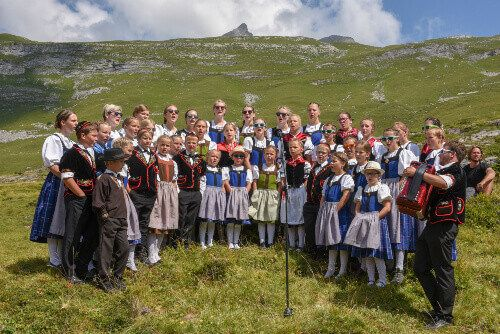 People wearing traditional swiss clothes yodelling at Engstlenalp on the Swiss Alps.
