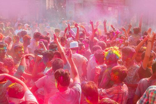 People covered with colorful paint for Holi festival in Udaipur.