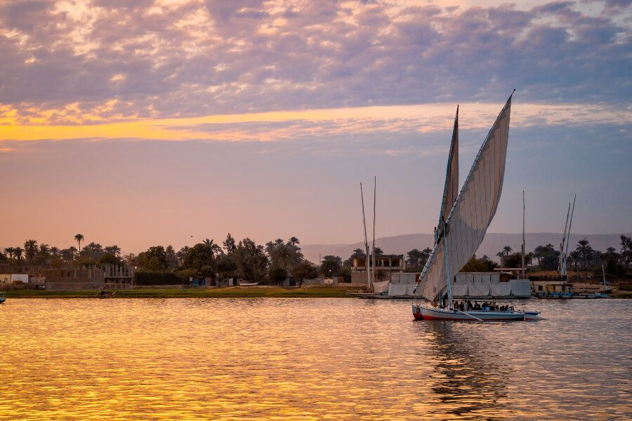 Felucca sailboat with tourists during a sunset in the Nile River