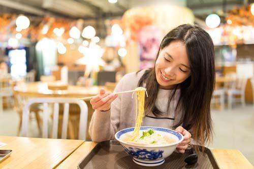 A woman eats a bowl of Ramen with chopsticks in Japan.