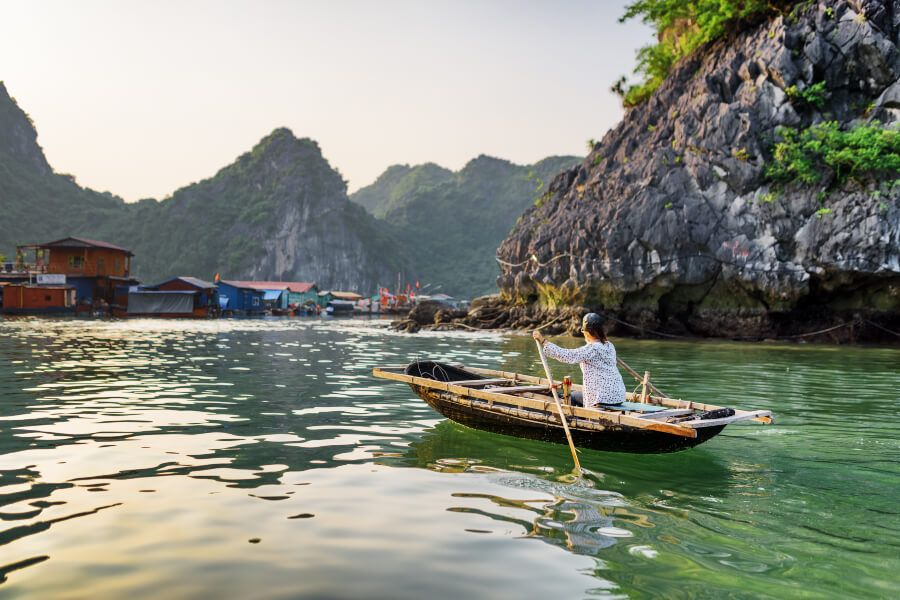 A female water hawker floating in the fishing village in Halong Bay.