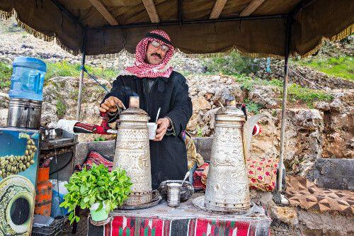 Bedouin man, traditionally dressed, preparing Bedouin mint tea in Ajloun.