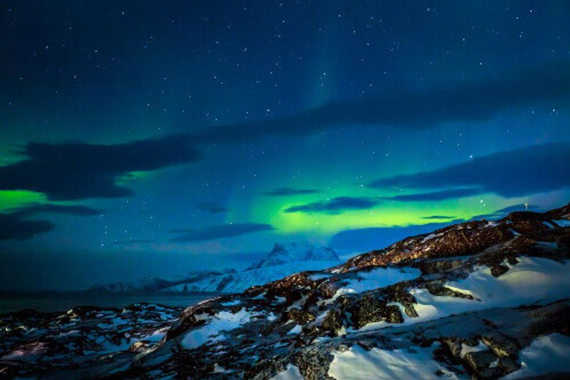 Northern Lights over the fjord and mountains in Nuuk.