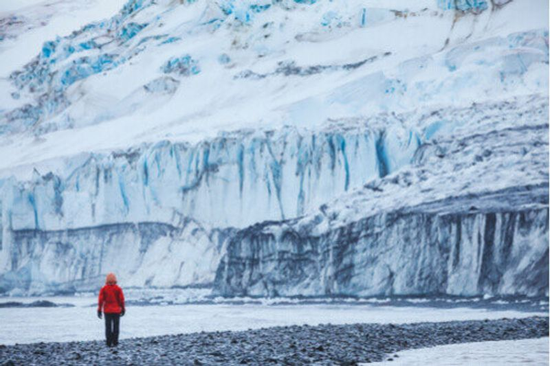 A person walks in front of a glacier in the Shetland Islands, Antarctica.