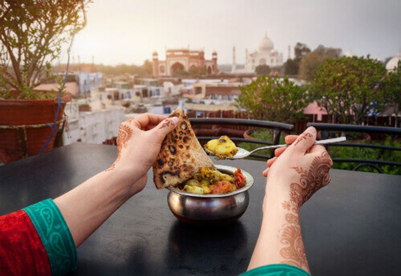 Visitors can enjoy traditional Indian food in rooftop restaurants with views of the Taj Mahal.