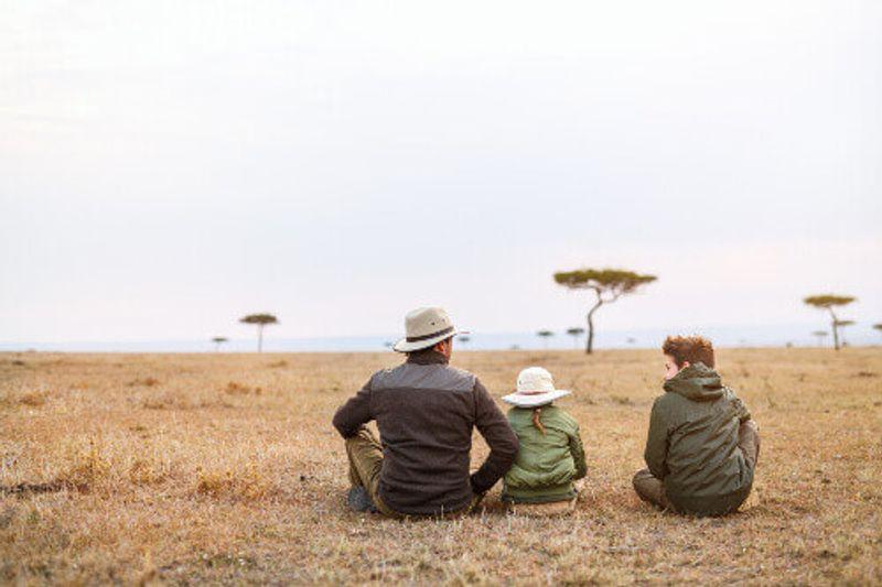 A family on an African safari vacation enjoying views over Masai Mara.