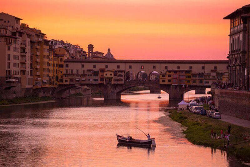 The Ponte Vecchio Bridge and vintage Barchetto Boat near the Arno River in Florence.