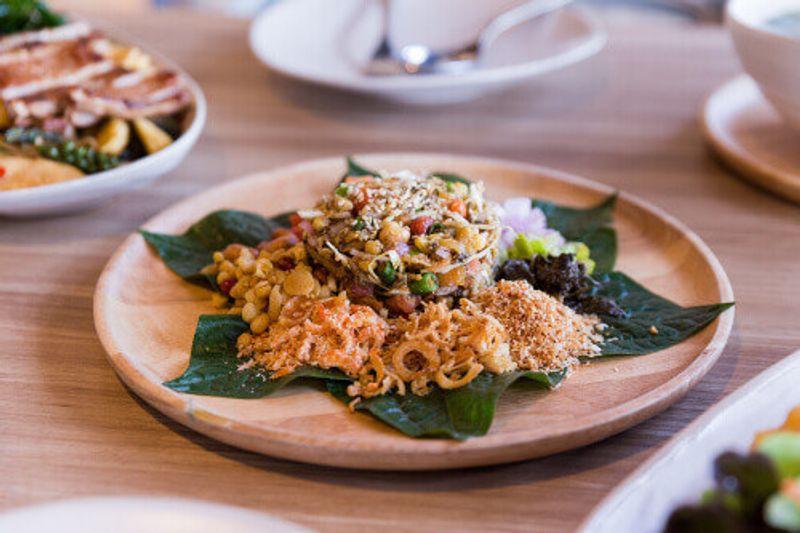 Lahpet is a Burmese Tea Leaf Salad served with deep fried garlic, peanut, white sesame, and dried shrimp.