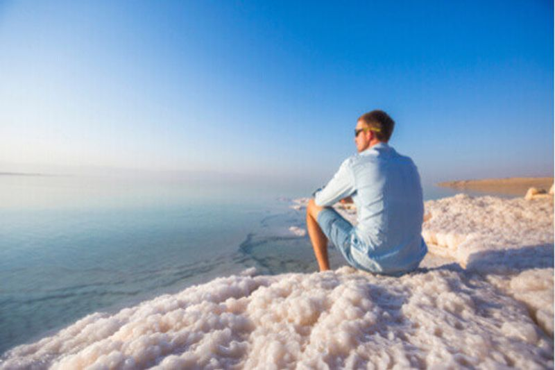 A male tourist sits on the shore of the Dead Sea.