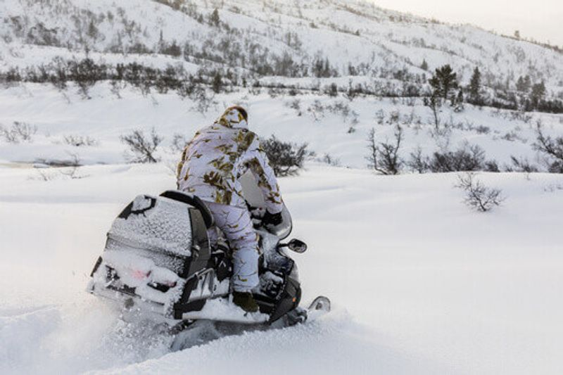 A man on a snowmobile during a safari experience.