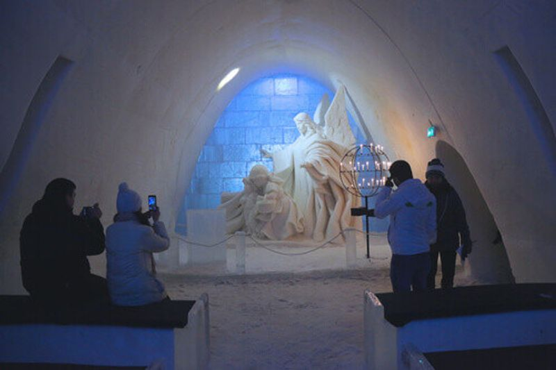 The stunning ice statues, with tourists taking photos at the Snow Castle in Kemi.