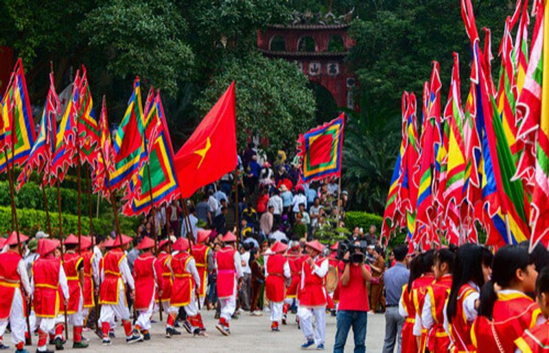 A procession of people in traditional clothing in Phu Tho, Vietnam.