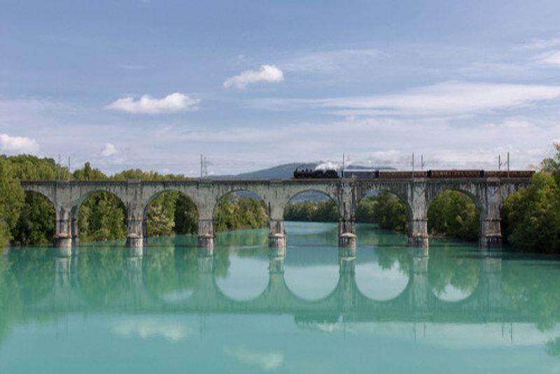 An Italian steam train passes over a stone arch bridge.
