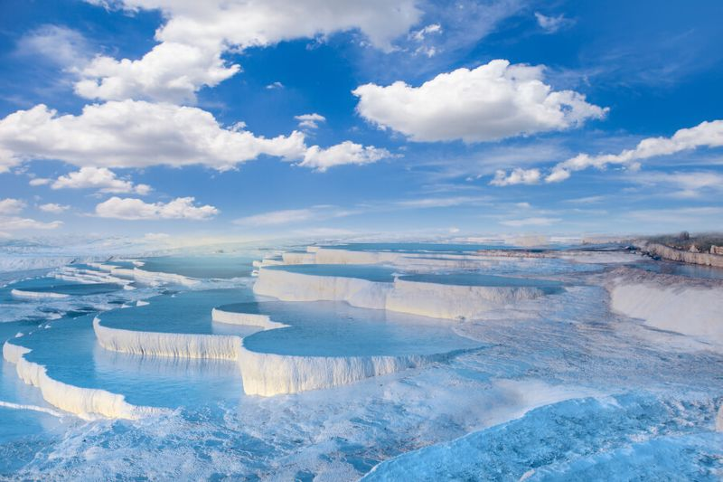The clear, reflective blue Pamukkale Pools invite tourists and locals year round.