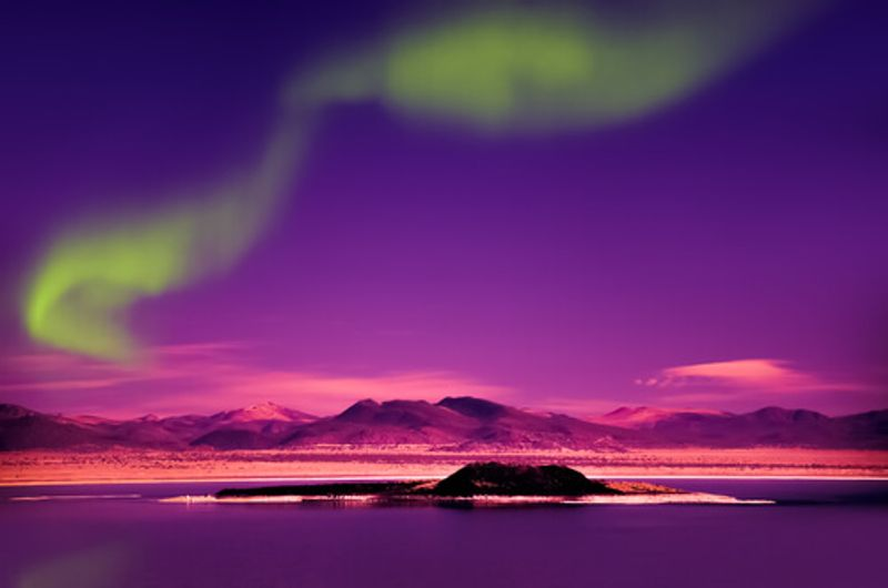 The phenomenon that is the Northern Lights, illuminates the night sky, dazzling visitors.