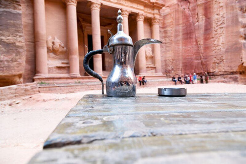 A traditional coffee sits on a table outside tourist attractions in Petra.