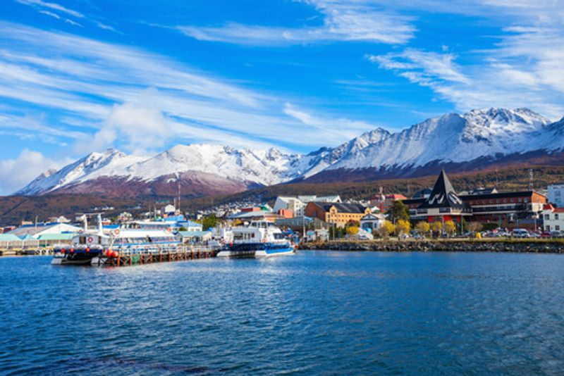 The bustling Ushuaia port where boats come and go against the backdrop of the mountain.